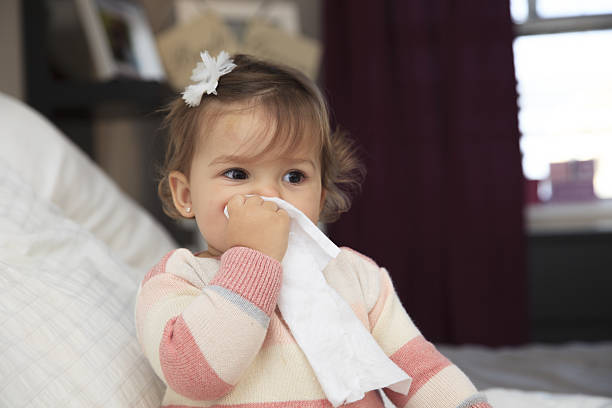 Little girl wiping her nose stock photo