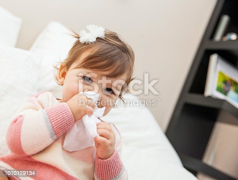 Little girl wiping her nose with a tissue