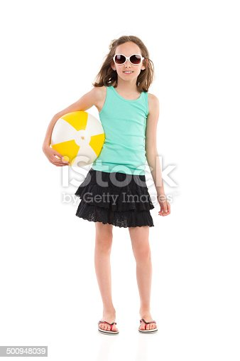 Young girl in teal shirt and black skirt posing with a beach ball under her arm. Full length studio shot isolated on white.