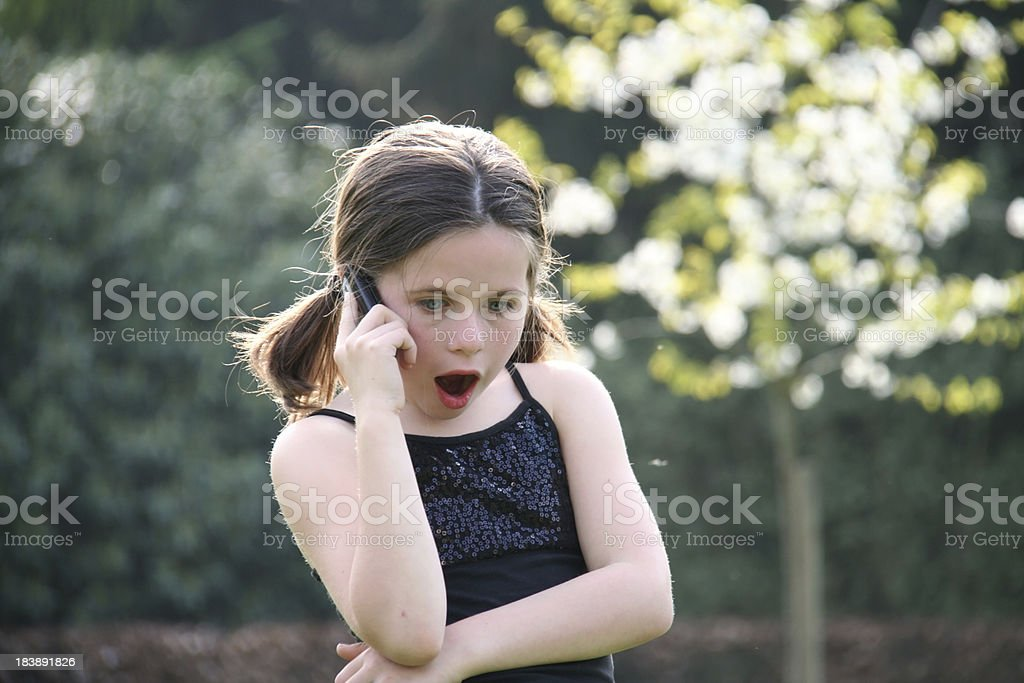 little girl with a cell phone stock photo
