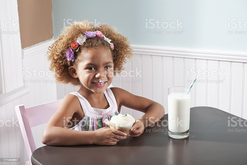 Little girl with a cupcake and glass of milk stock photo
