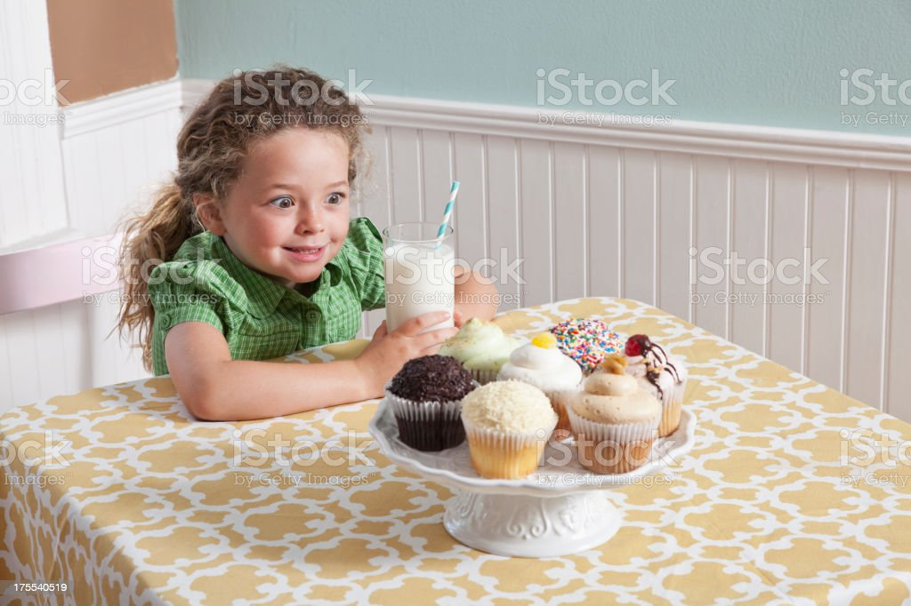 Little girl with a glass of milk and cupcakes stock photo