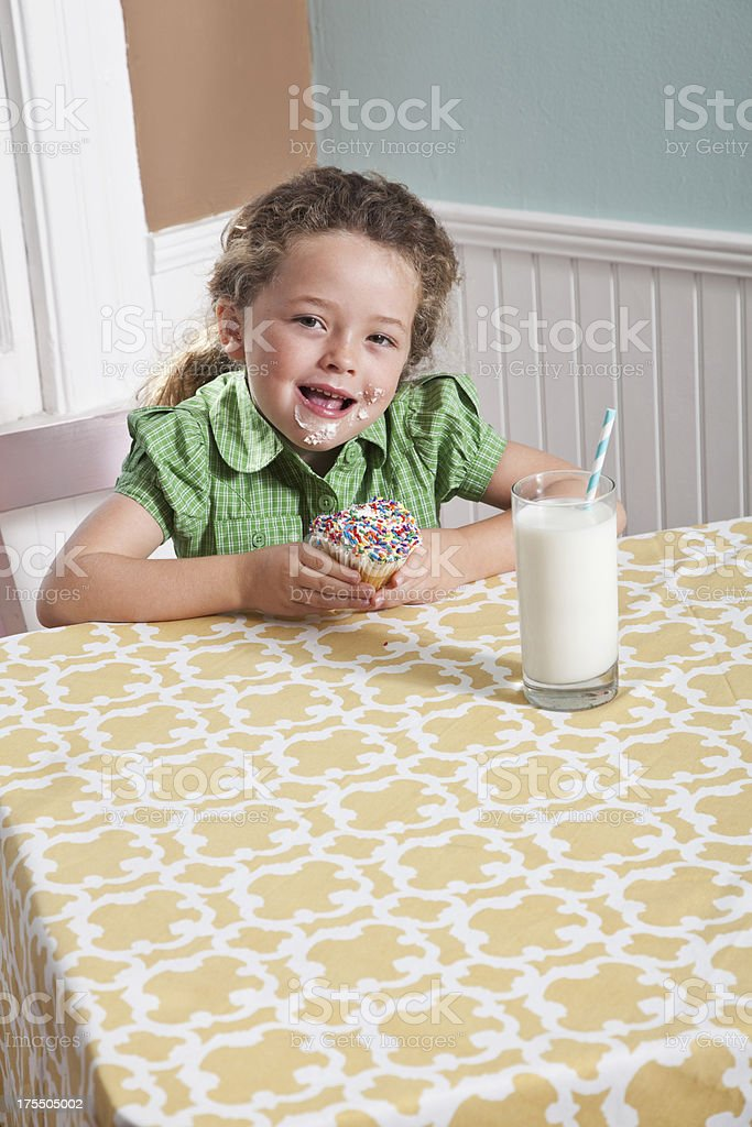 Little girl with a glass of milk eating cupcake stock photo