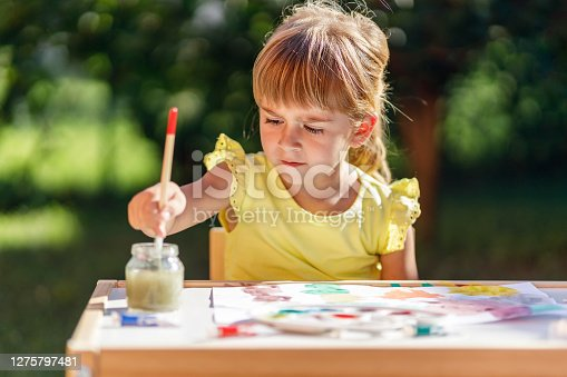 A cute little blond girl getting the paintbrush ready for new colors by dipping it in water