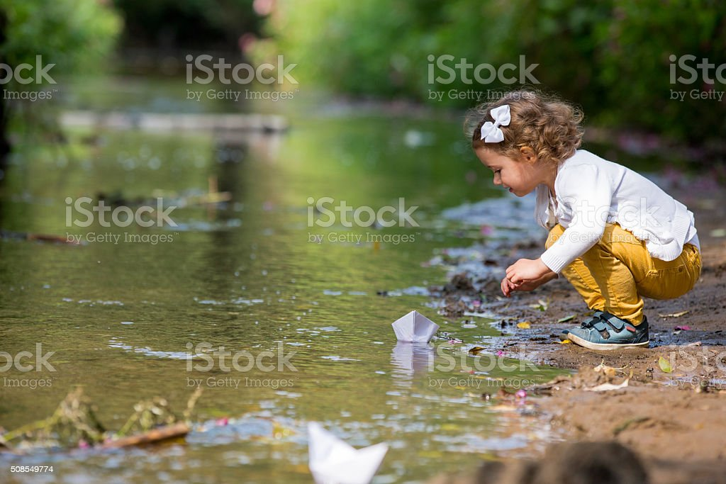 Little girl with a paper boat stock photo