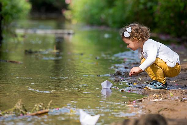 kleines mädchen mit papier boot - kinder picknick spiele stock-fotos und bilder
