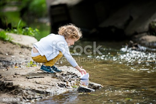 istock Little girl with a paper boat 508551928