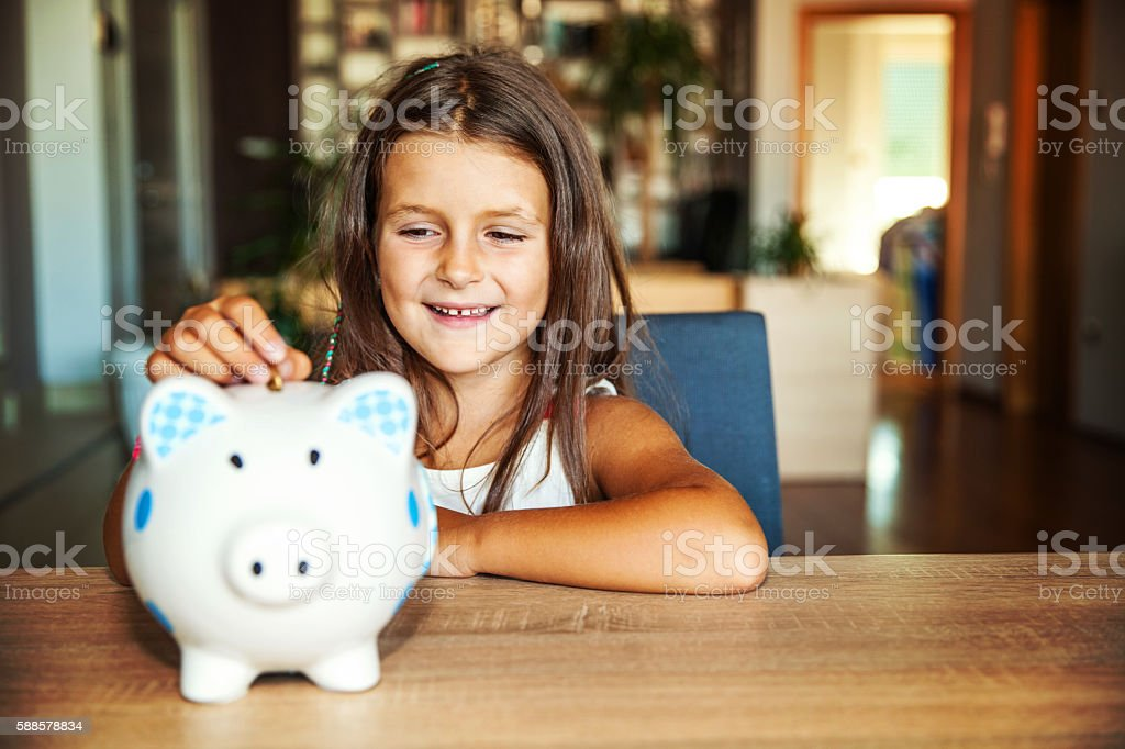 Little girl with a piggy bank at home stock photo