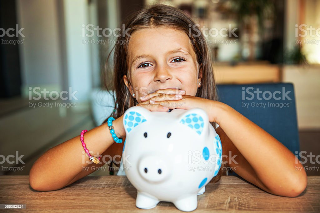 Little girl with a piggy bank at home – Foto