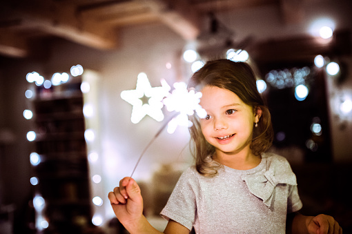 Little girl with a sparkler at Christmas time.