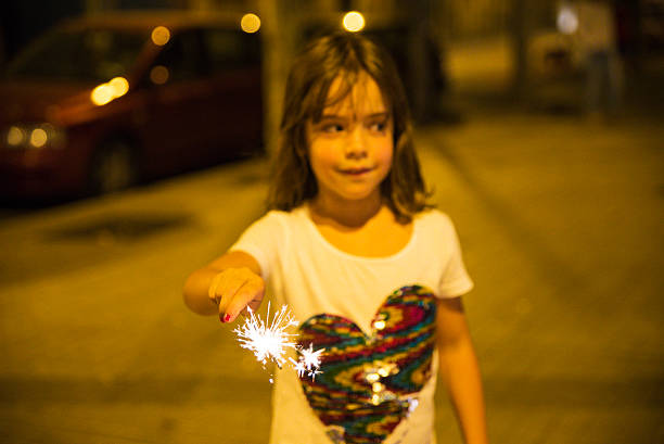 little girl with a sparkler, barcelona - petard stock photos and pictures