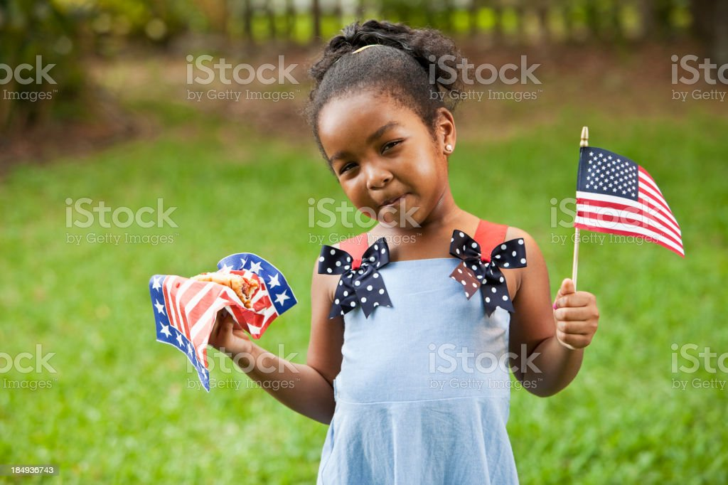 Little girl with American flag and hotdog stock photo