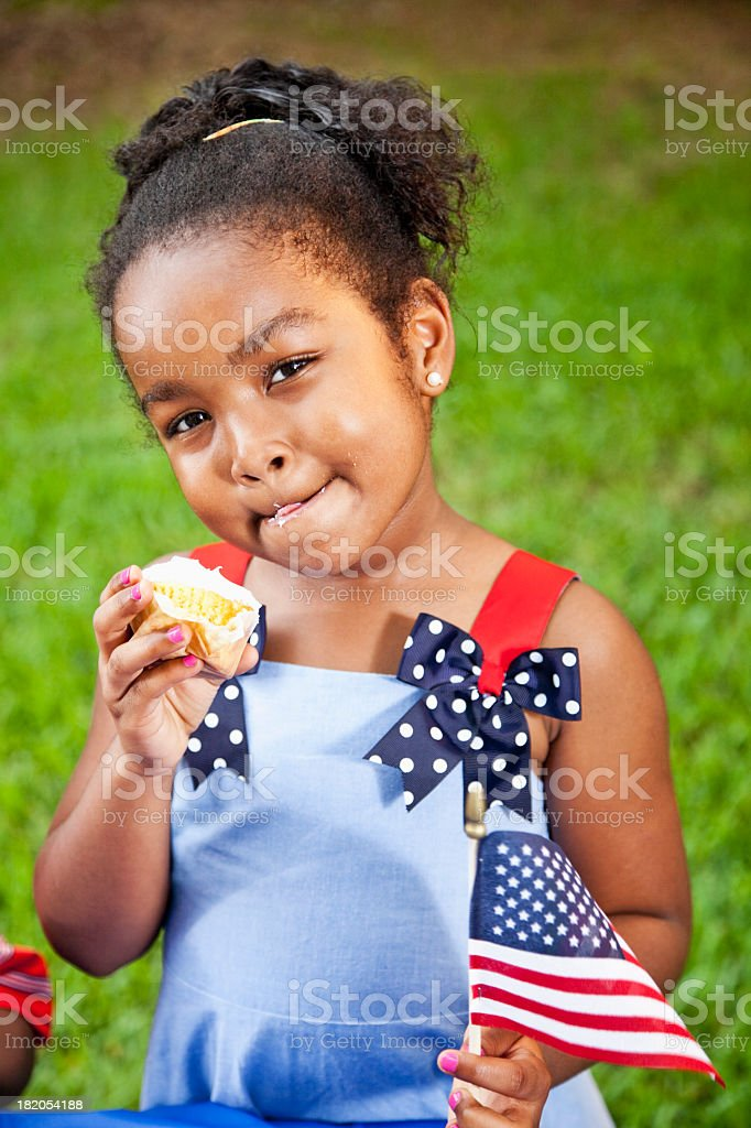 Little girl with American flag eating cupcake stock photo