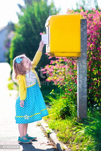 istock Little girl with an envelope next to a mail box 474320420