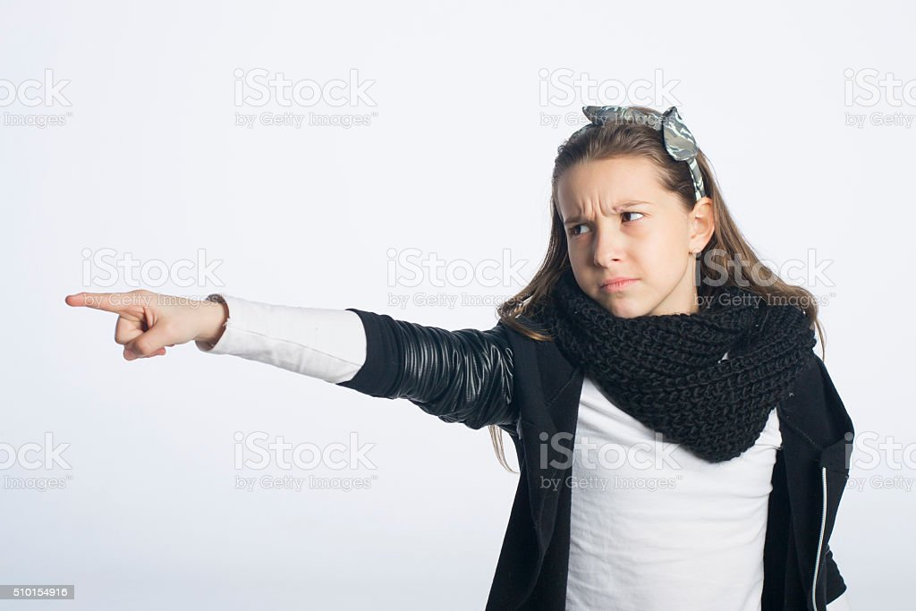 Little girl with angry facial expression pointing with her finger stock photo