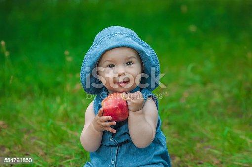 istock Little girl with apple. 584761850