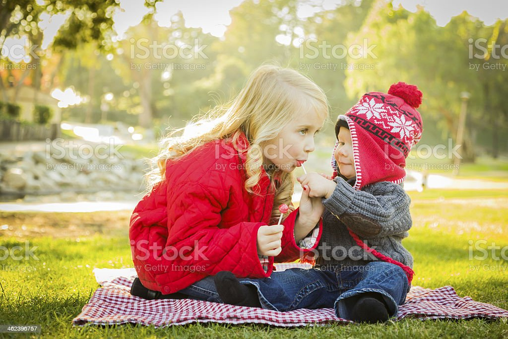 Little Girl with Baby Brother Wearing Coats and Hats Outdoors stock photo