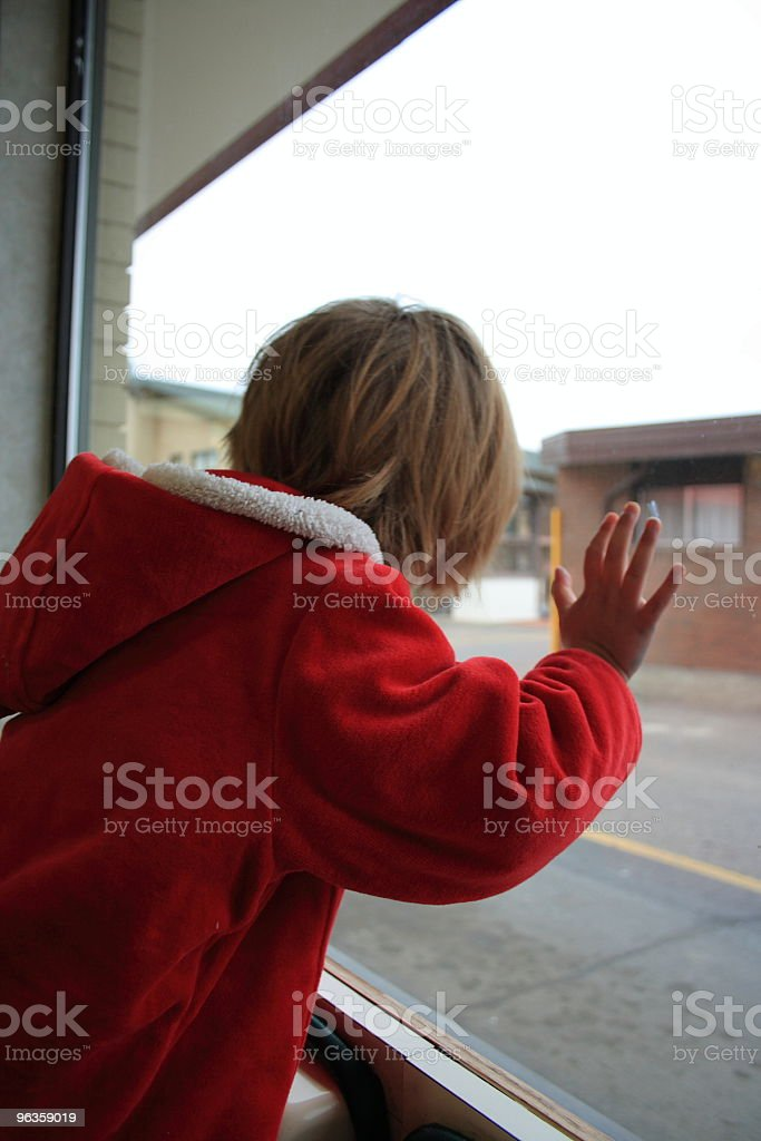 little girl with back to camera looks out big window royalty-free stock photo