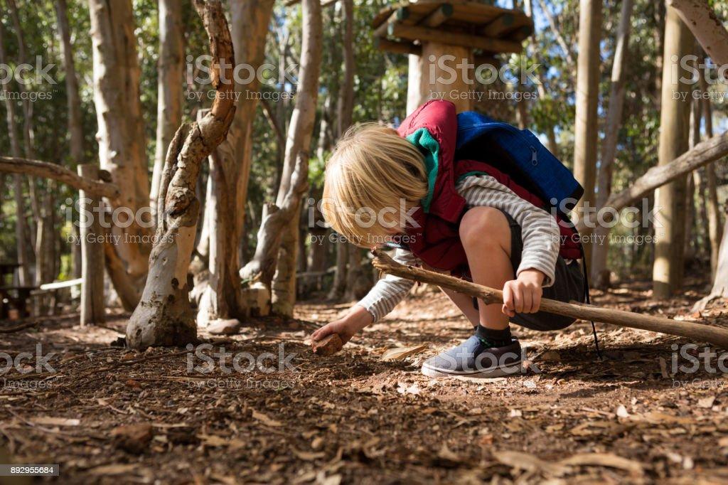 Kleines Mädchen mit Rucksack mit Stock in der Hand spielen mit rock – Foto