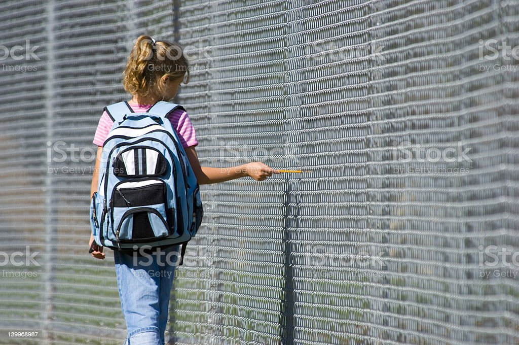 Little girl with backpack walking to school stock photo