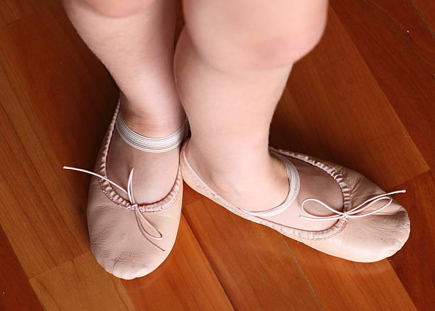 Little girl with ballet shoes standing in third position stock photo