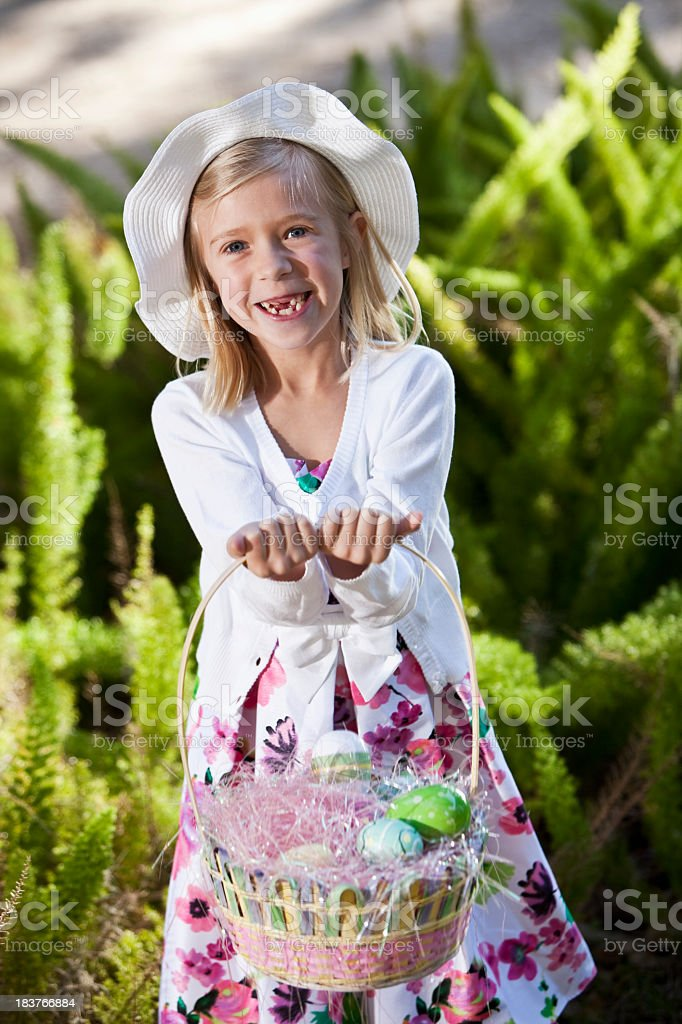 Little girl with basket of easter eggs stock photo