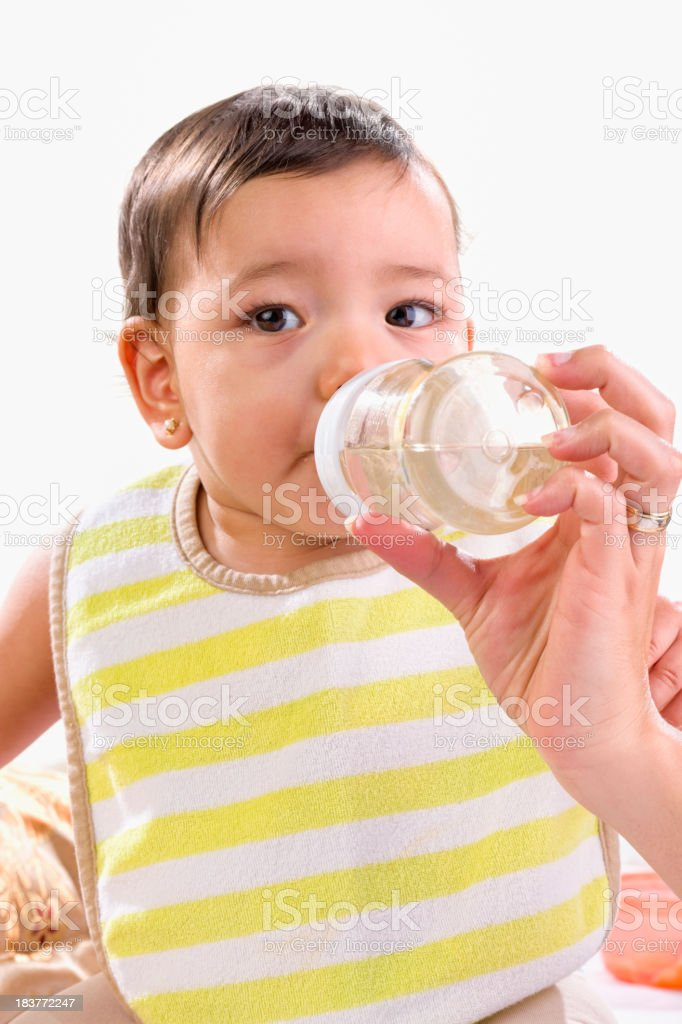 Little girl with bib drinking water on a baby bottle royalty-free stock photo
