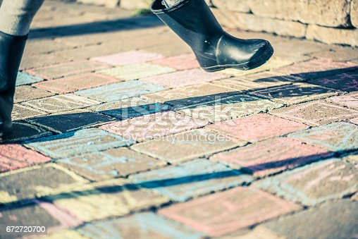 istock Little girl with black robber boots playing on paved sidewalk after drawing with chalk 672720700
