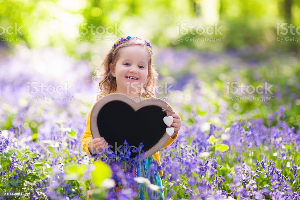 Little girl with blank board in flower field stock photo