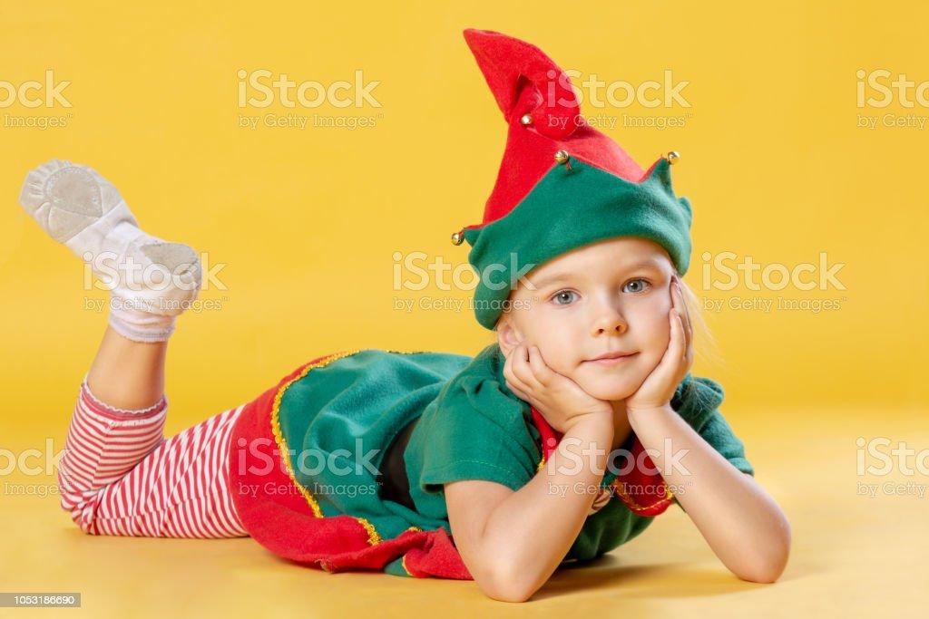 8bfb49874e648 Petite fille aux cheveux blonds dans un costume de lutin de Noël. Le bébé  est