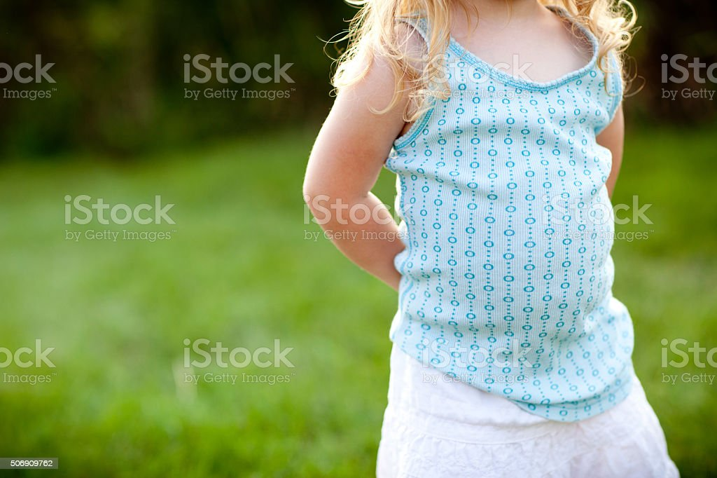 Little Girl with Blond Hair Waiting Patiently Standing Outside stock photo