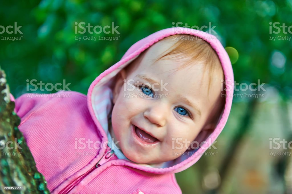 Little girl with blue eyes peered out from behind tree stock photo
