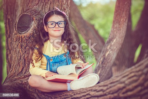 Child sitting on a tree branch with a book in autumn