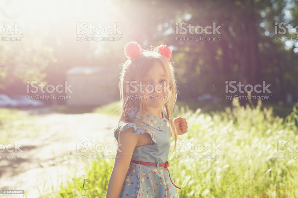 Little girl with bows in park stock photo