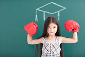little girl with boxing gloves and graduation concept