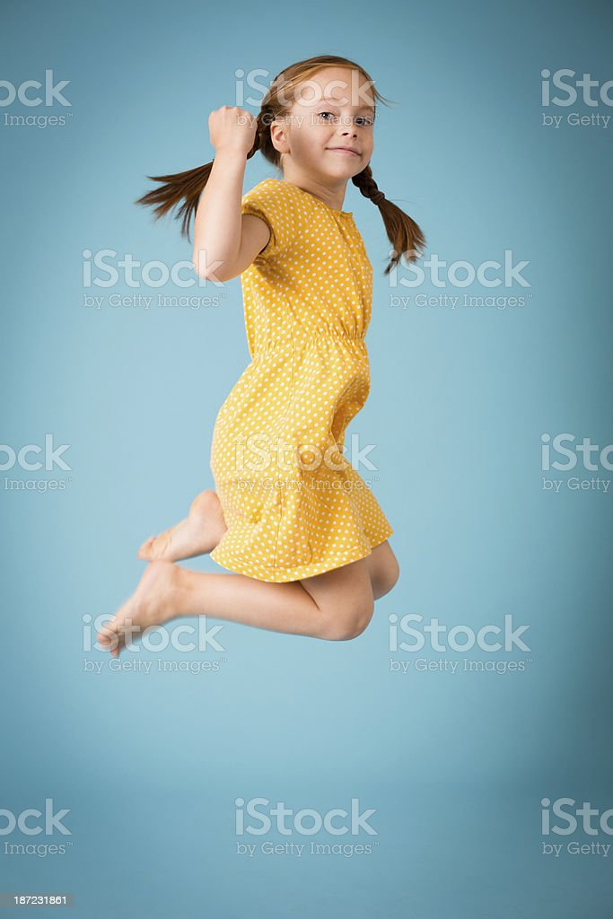 Little Girl With Braided Red Hair Jumping Up in Air stock photo