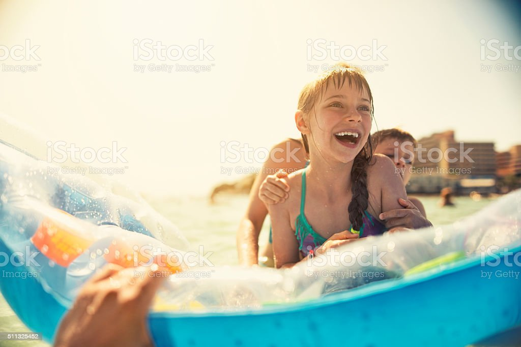 Little girl with brother and mother having fun in sea stock photo