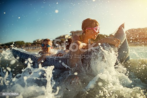 istock Little girl with brothers having fun in sea 602328654