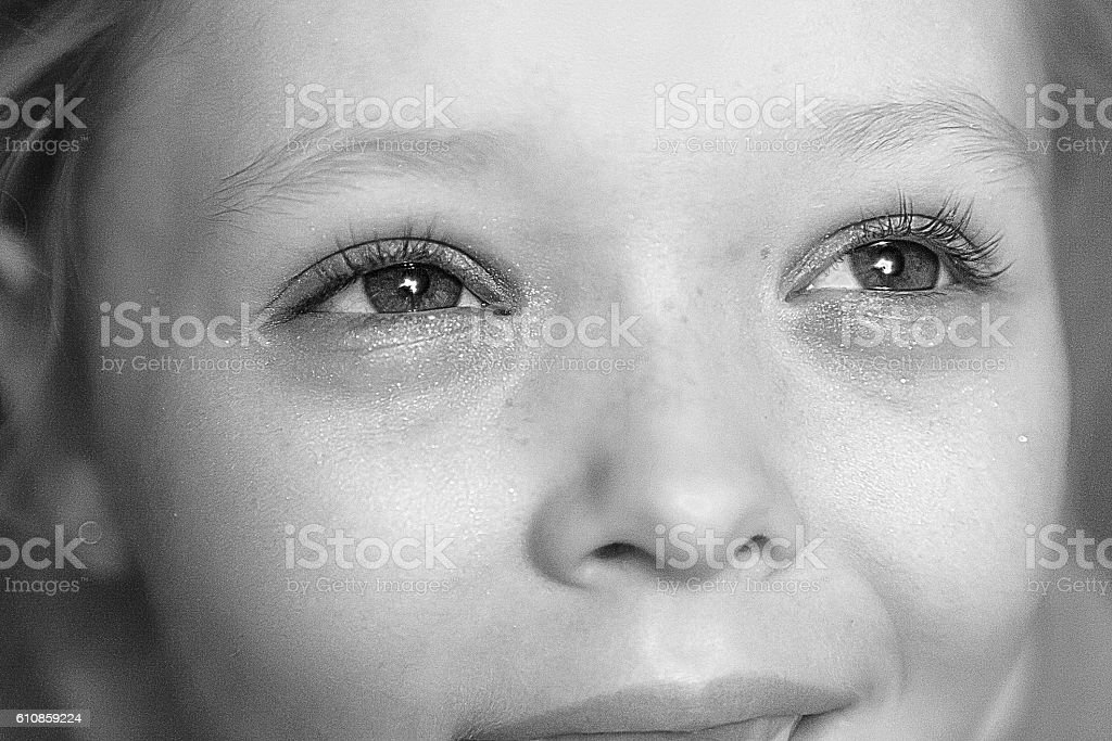 Little girl with brown eyes in black and white stock photo