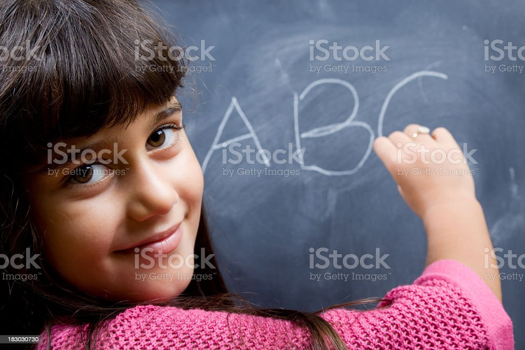 Little Girl With Brown Hair And Eyes Posing While Writing royalty-free stock photo