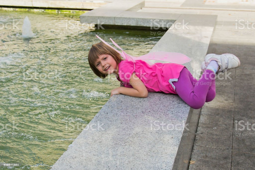 Little girl with butterfly wings having fun in a fountain.