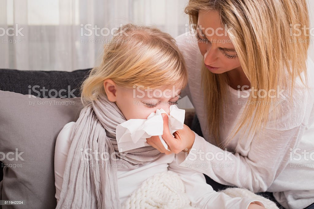 Little girl with cold and blowing her nose stock photo