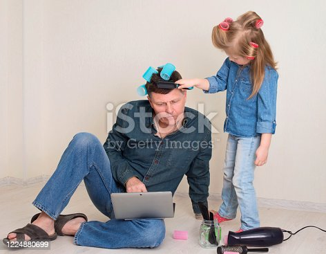 Little girl with colorful hair curlers making funny hairstyle for her father. Preschooler girl brush hair of her mature dad and play as if she works in a beauty salon while father is working on his laptop. Family, happy parenting and working at home concept. Being father of daughter.