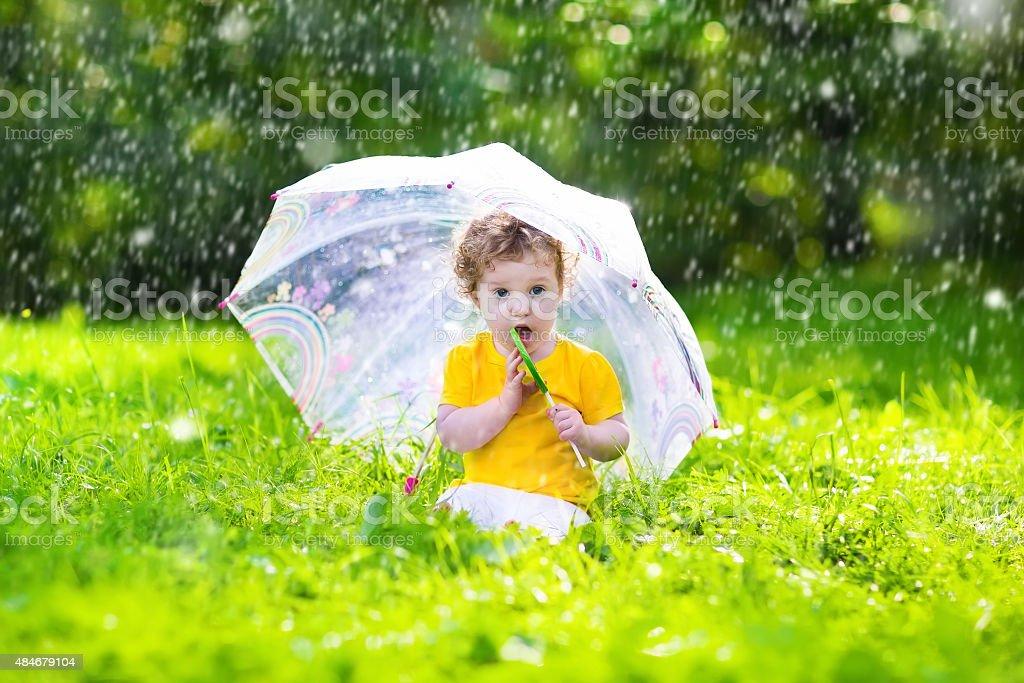 Menina com um guarda-chuva colorida brincando na chuva - foto de acervo