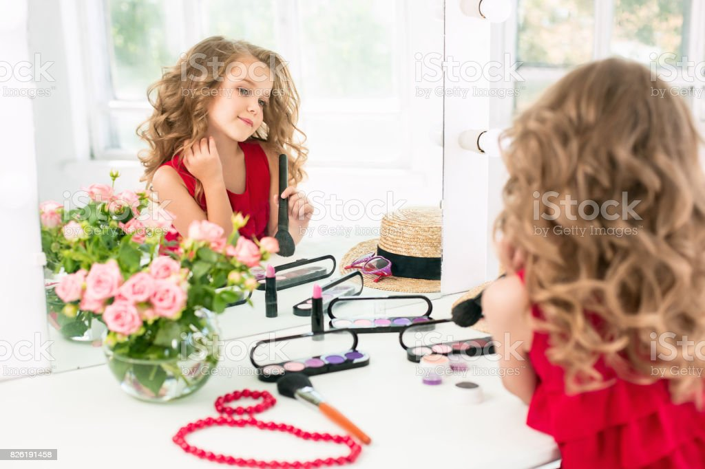 A little girl with cosmetics. She is in mother's bedroom, sitting near the mirror stock photo