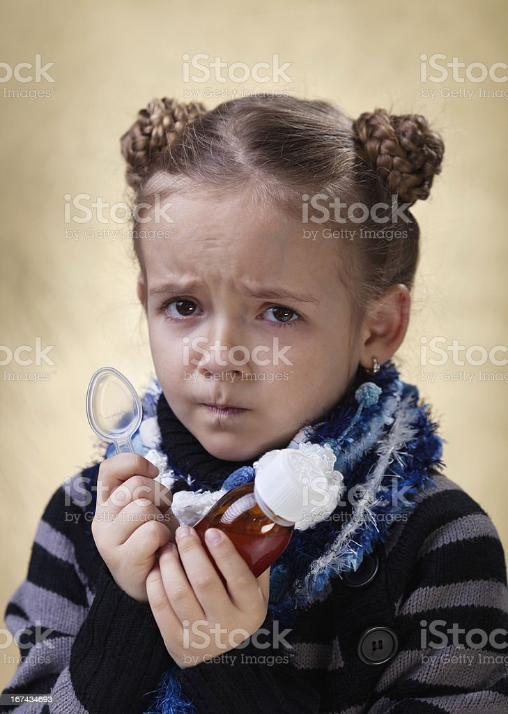 Little girl with cough medicine having a worried look royalty-free stock photo