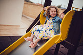 Happy little girl having fun playing at kindergarten playground and sliding down slide