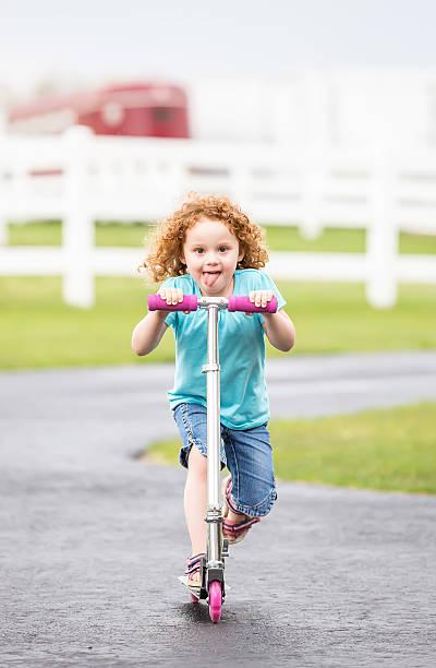 kleines mädchen mit lockiges rotes haar reiten roller - denim caprihosen stock-fotos und bilder