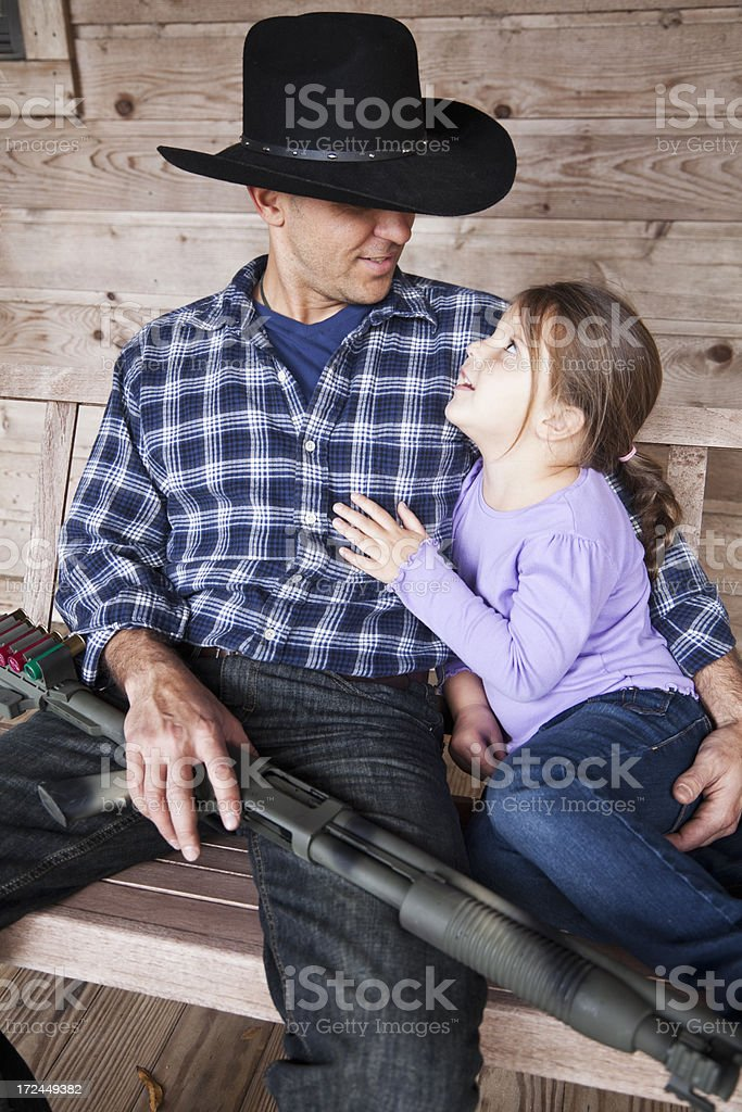 Little girl with dad holding shotgun royalty-free stock photo
