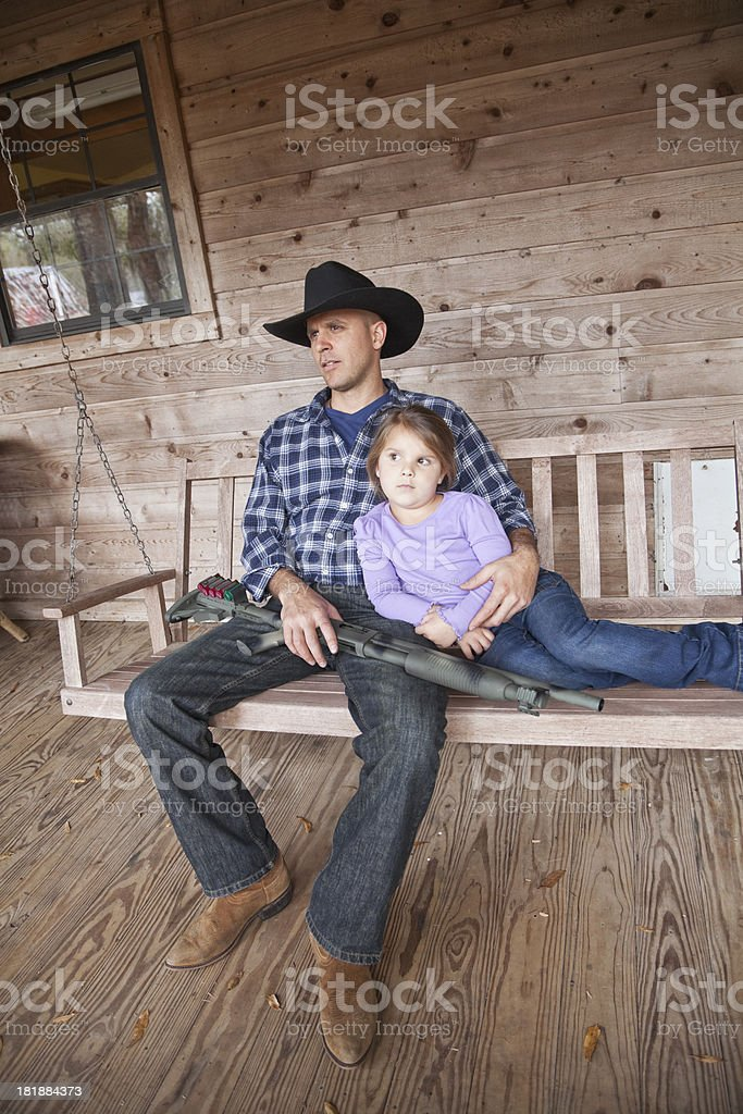 Little girl with dad holding shotgun stock photo
